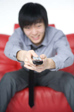 The smiling young man in a grey shirt watches TV photo