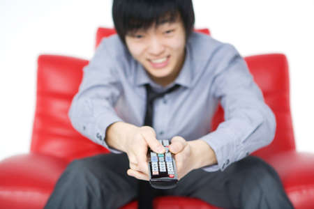 tv remotes: The smiling young man in a grey shirt watches TV