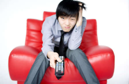 The young man in a grey shirt watches TV