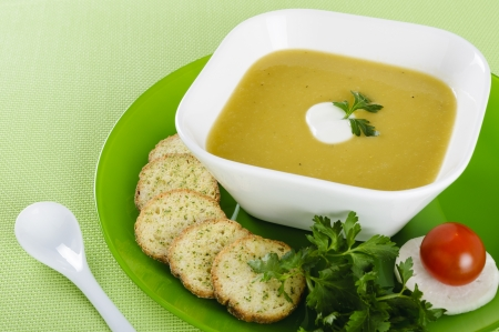 Vegetable cream soup with crackers, parsley, radish and tomato photo