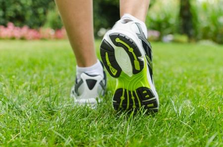 Woman running on green grass in summer