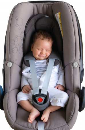 Newborn boy is sleeping and smiling in a car seat photo