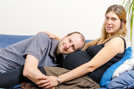 Smiling man embracing happy pregnant woman sitting on couch holding tummy