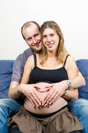 Happy parents make heart sign with two pairs of hands on pregnant woman's belly sitting on couch Stock Photo - 23890191