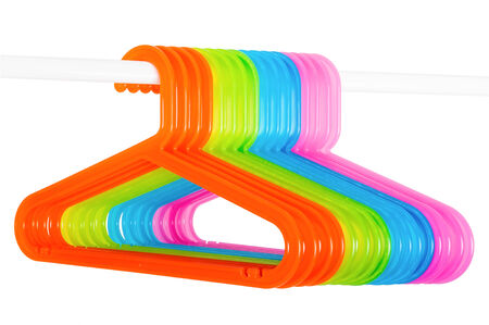 Colored plastic hangers hanging on a rod isolated on white background photo