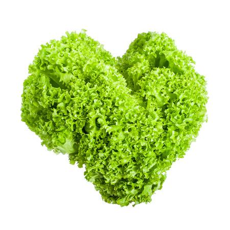 Fresh lettuce leaves in a heart shape isolated on white