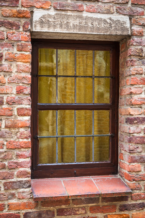 transom: Window of a medieval building with very old brick wall