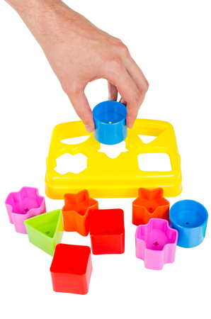 Human hand puts wrong shape into shape sorter toy with various coloured blocks isolated on white background Imagens