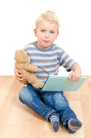 Cute little blond boy holding his teddy bear and a book isolated on white background