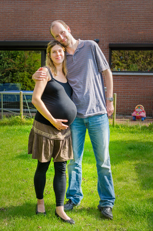 Couple with pregnant wife in the garden in front of their house Imagens
