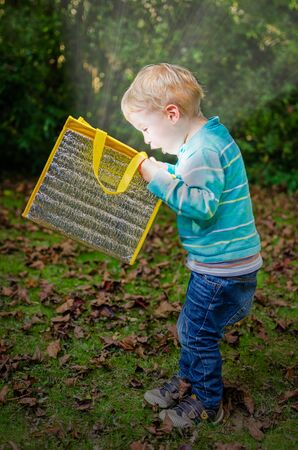 Cute surprised little blond boy is looking inside a bag with glow light