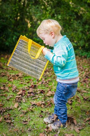 Cute surprised little blond boy is looking inside a bag at park