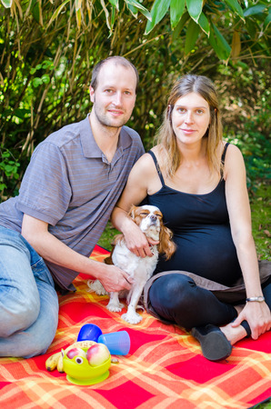 Happy beautiful family with their dog and pregnant mother outdoors at the park