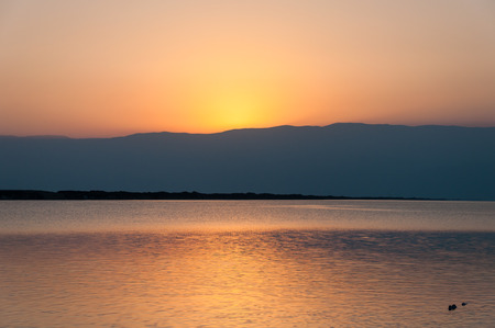 Sunrise over Jordan mountain Dead Sea shore with sun ray reflection on water surface in Israel photo