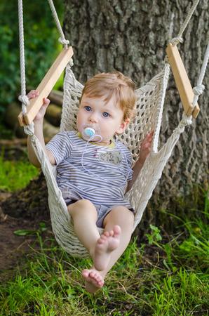 Little cute baby boy riding on a hammock swing in the park