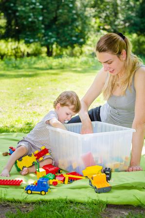 people together: Pequeño muchacho lindo bebé juega los juguetes con la joven y bella madre en el parque