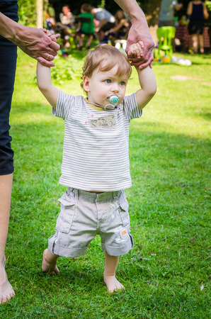 Little cute baby boy learning to walk by holding his mothers hands in the park Imagens