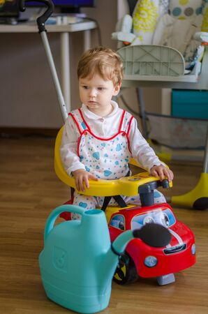 Beautiful cute little boy riding a sport toy car at home