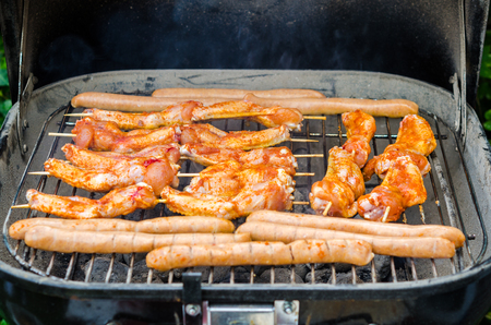 Sausages and chicken wings on the smoking grill barbeque photo