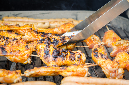 grill tongs sausage: Sausages and chicken wings on the smoking grill barbeque Stock Photo