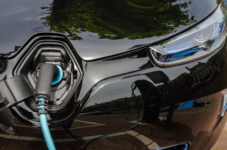 plugged in': Charging modern electric car with the power supply plugged in Stock Photo