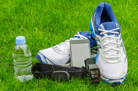 Modern sport equipment for running on the grass. Sneakers, water, smartphone, sport watch and heart sensor photo