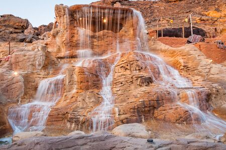 waterfall with sky: The waterfall on a red rock in Egypt in summer Stock Photo