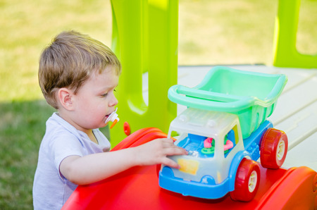 Cute little boy plays with toy car at park in the summer