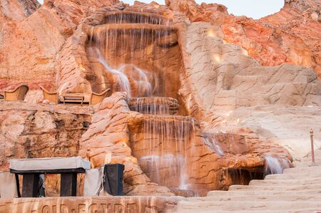 The waterfall on a red rock in Egypt in summer Imagens