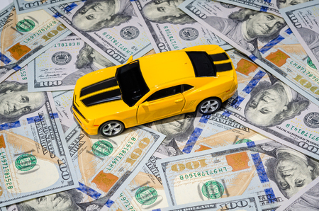 economic rent: Yellow sport car on american dollars bills paper money background Stock Photo