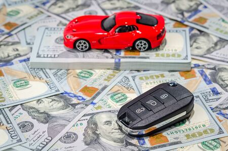 Red sport car with keys on american dollars bills paper money background