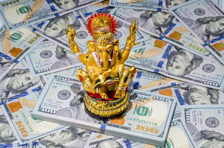 Hindu Ganesha god of wisdom on top of the money american dollars bills Imagens
