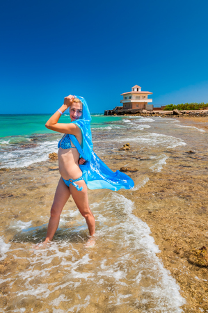 Full length portrait of beautiful girl with blue scarf on the beach. Concept for travel and vacation