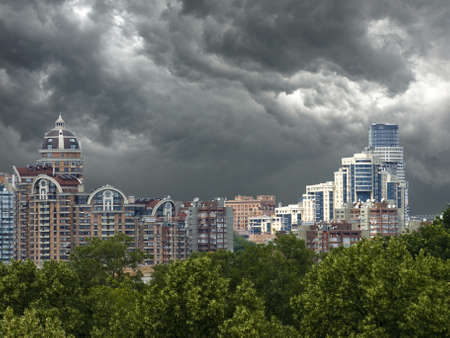 City landscape before the storm. Constructed and built high-rise buildings, trees and above the storm clouds. Stock Photo