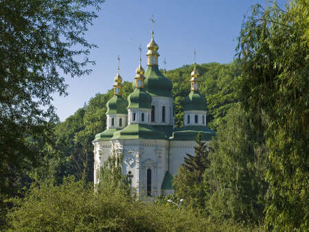 Summer. Middle of the verdure-covered hills are visible dome of the Cathedral of St. George Vydubychi monastery, Kiev, Ukraine. Stock Photo - 13977380