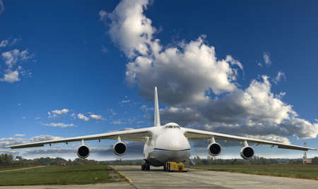 Large cargo plane at the airfield  The ladder is lowered  In front aircraft is towing vehicle  Against the background of sky and clouds  Editorial
