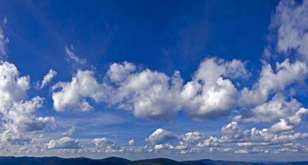 The sky over the hilly terrain  With white and gray cumulus and cirrus clouds  On top of the blue sky