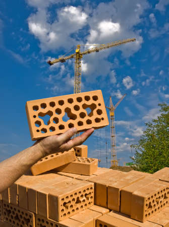pallet of lightweight bricks. In the palm of your hand is a brick. Against the background of the two tower cranes.
