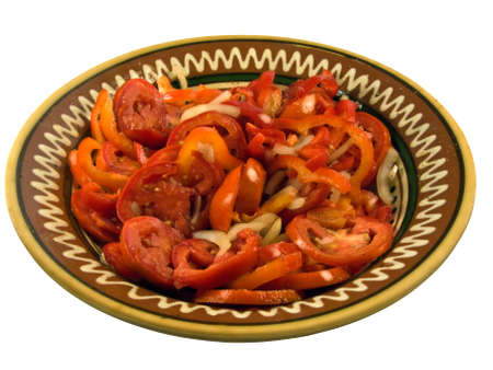 salad with fresh tomatoes and peppers in a brown ceramic salad bowl in the ethnic style Stock Photo