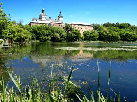 The pond is surrounded by trees and  water-lilies. The water reflected the trees, the roofs of houses and churches.