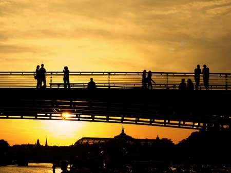 Sunset. Silhouettes of the buildings on the shore, the bridge and the people on the bridge. The sun shines through the beams of the bridge. photo