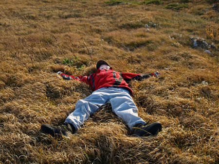 Autumn. A boy in a tracksuit and cap flopped in the grass. photo