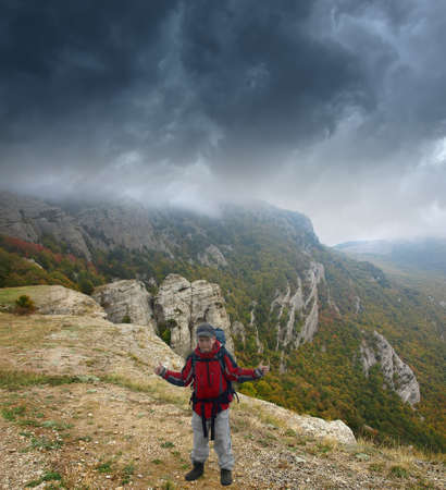 nuisance: Teen shows on the storm clouds gathering behind him. Autumn. Mountains. Hiking. Stock Photo