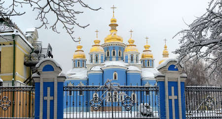 Winter day  St  Michael s Golden Domed Cathedral,  Kiev, Ukraine  On the branches of a tree, on the lattice fence, on the domes and on the slopes of roofs lies thick layer of snow  Stock Photo - 16423820