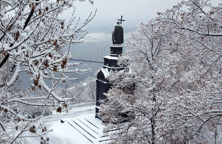 Monument to Prince Vladimir, the Baptizer of Rus in Kiev, Ukraine. Overcast winter day. All covered with snow. View of the Dnieper River.