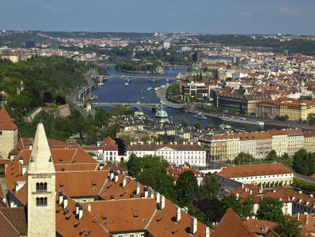 stefanik: The view from the bell tower of the Cathedral of St. Vitus in the north-east - to the river Vltava, Chekhov bridge, Stefanik, Josefov, island Stvanice. Czech Republic, Prague. Red tiled roofs, the river, the bridges.