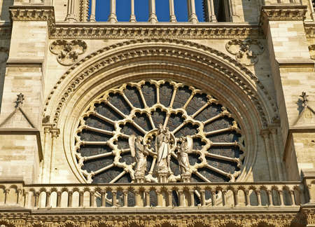 Central rosette on the facade of the cathedral of Notre Dame, Paris, France  Stained-glass and sculpture of our lady