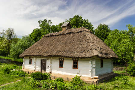 ethnographical: Authentic farmhouse of historical area of Podolia, 19th century  Wooden house with thatched roof  The biggest open air museum in Europe - National Museum of Ukrainian Architecture and Culture Pyrogovo, Kiev, Ukraine  Stock Photo