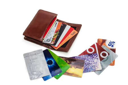 wallet with discount cards and next are a few cards. over white