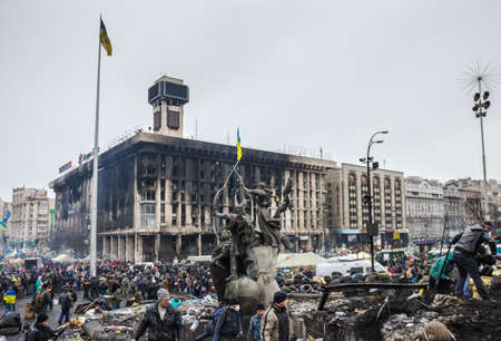 collisions: Kiev, Ukraine - February 22, 2014  the burnt house of Trade Unions  and Maidan after the cessation of collisions  People, tires, fumes and soot